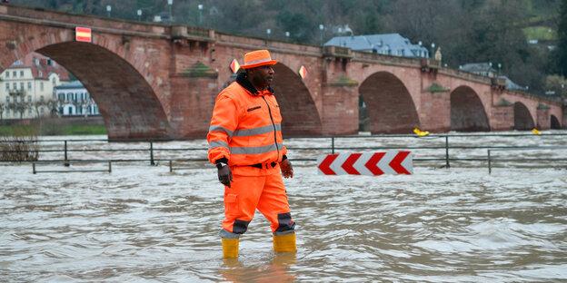 Ein Mann steht im Hochwasser des Neckars bei Heidelberg