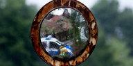 Ein Fahrzeug der Polizei ist in einem alten Spiegel zu sehen