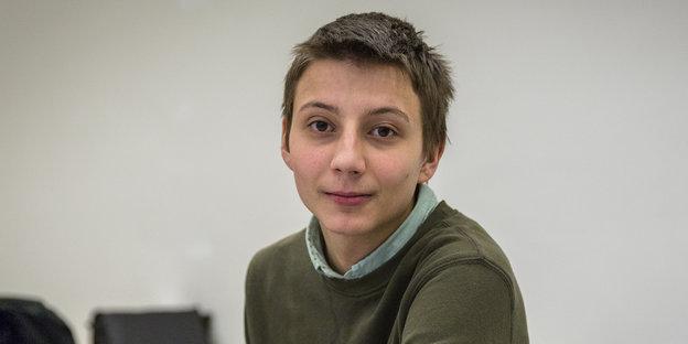 Ein junger Mann mit kurzen hellbraunen Haaren, einem grünen Hemd und einem dunkelgrünen Pullover darüber.