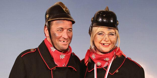 Ulrike Scharf und ein Begleiter verkleidet als Feuerwehsleute