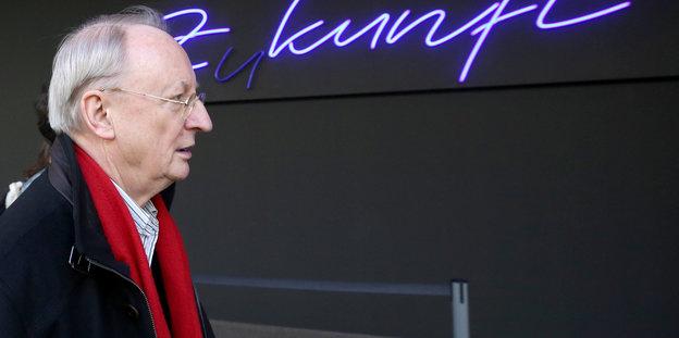 """ein Mann mit rotem Schal vor der Leuchtschrift """"Zukunft"""""""