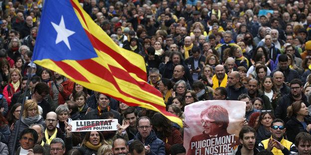 Demonstranten zeigen ein Transparent mit Puigdemonts Gesicht und die katalanische Flagge