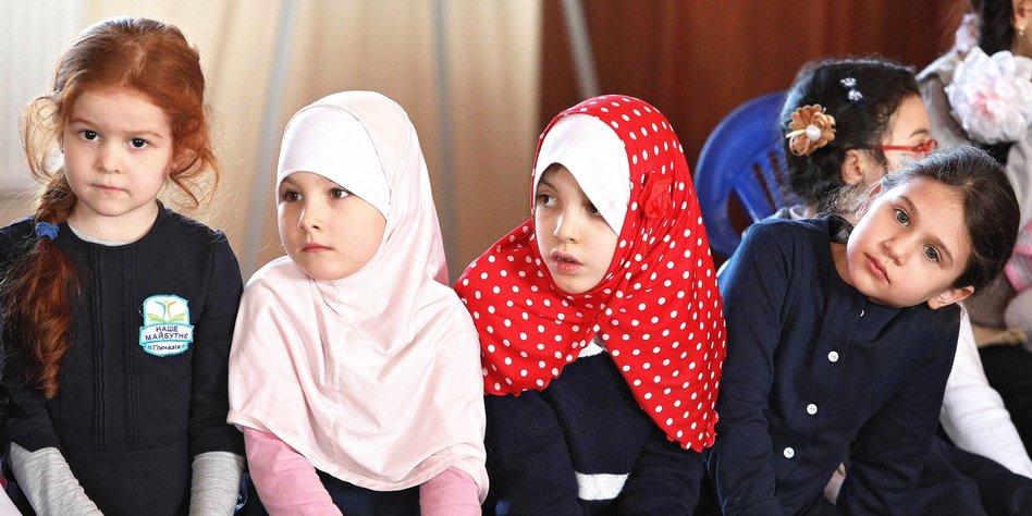 459fe89d59 Vier kleine Mädchen im Vorschulalter sitzen nebeneinander, die zwei in der  Mitte tragen Kopftücher