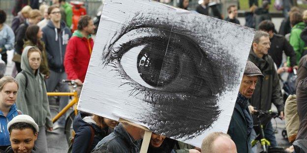 Demonstranten und ein Plakat mit einem Auge