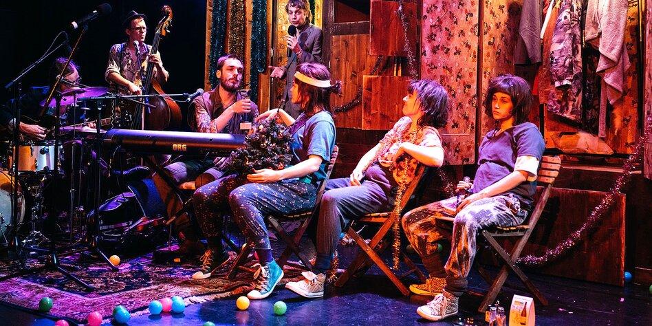 Mehrere Menschen Auf Einer Bühne, Einige Mit Instrumenten, Einige Sitzen,  Andere Stehen