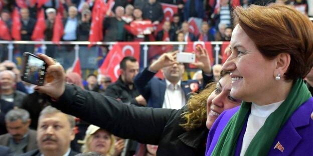 Eine Frau macht mit einer anderen ein Selfie, im Hintergrund türkische Flaggen