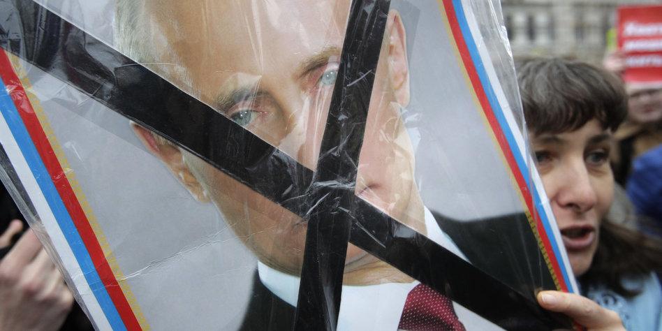 Eine Frau hält ein Schild hoch auf dem Putin durchgestrichen ist