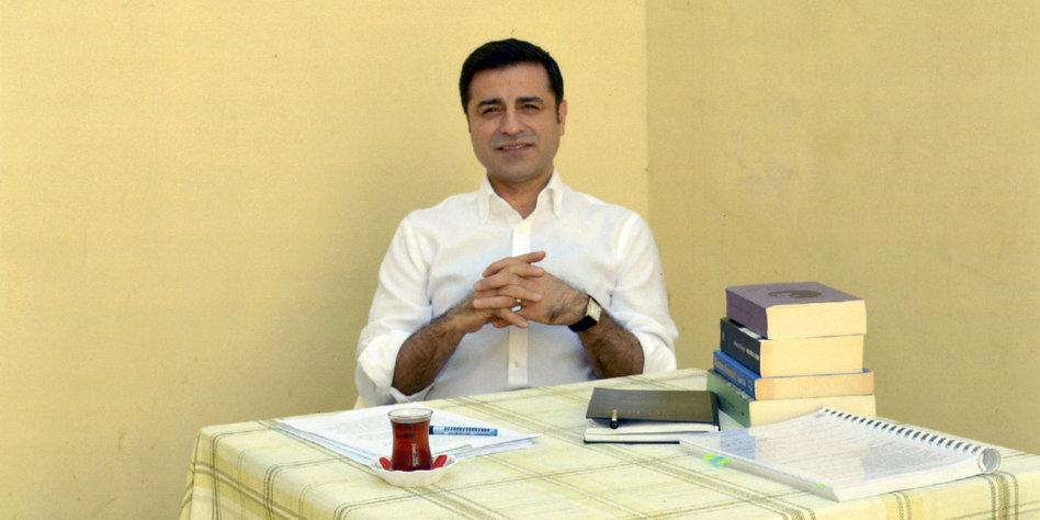 Selahattin Demirtaş sitzt an einem Tisch, auf dem ein Stapel Bücher liegt und eine Tasse Tee steht