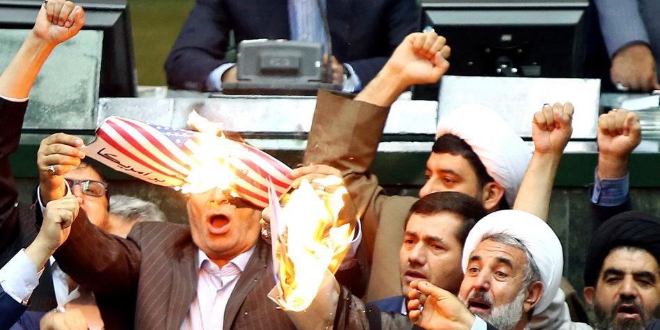 Wild gestikulierende Männer mit einer brennendem Papier