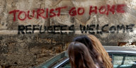 "Graffiti ""Tourist go home"" an einer Wand"