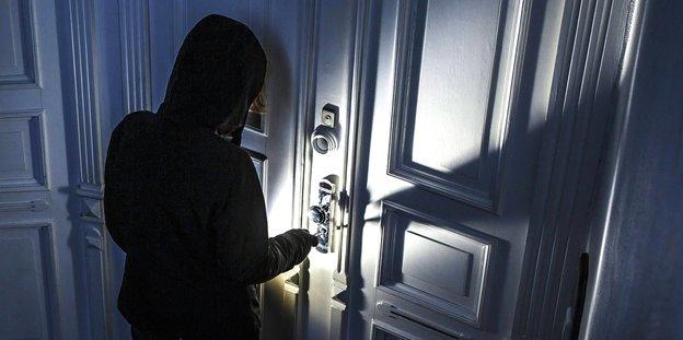 eine schwarz gekleidete Person vor einer Tür