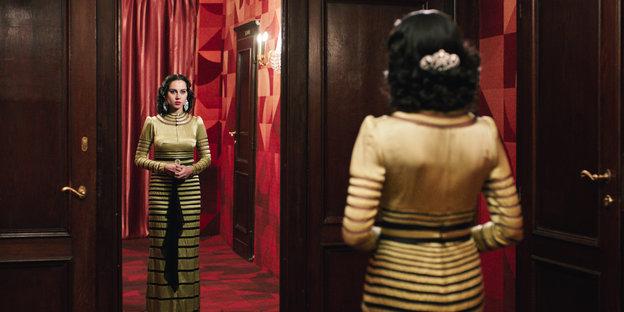 Eine Frau im eleganten Kleid vor einem Spiegel