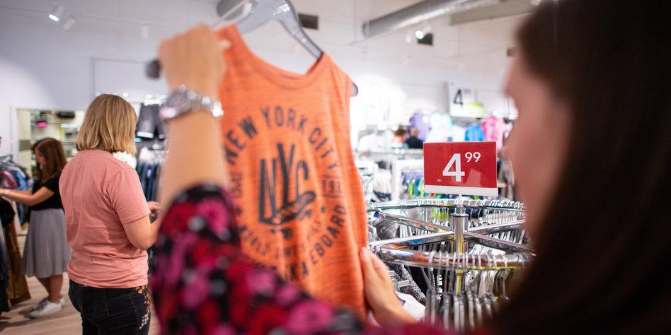 15c1db29e99401 Eine Frau betrachtet ein organgenes Shirt