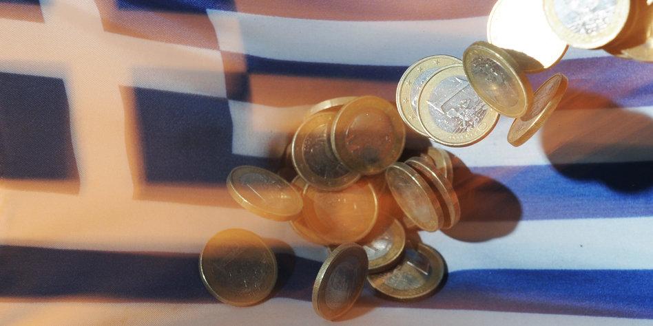 Euromünzen fallen auf eine Griechenlandflagge