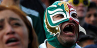Ein mexikanischer Fan mit Fan-Maske jubelt in Mexiko City.