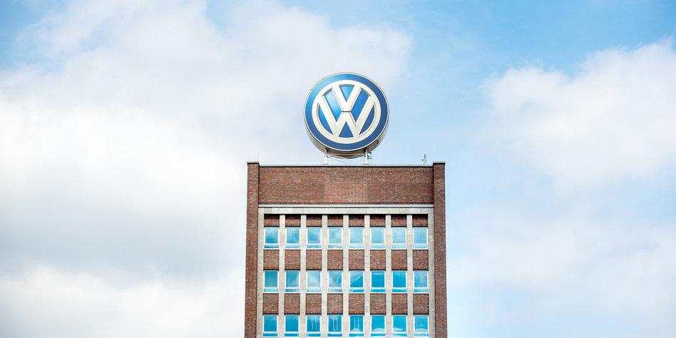 Hochhaus mit VW-Emblem dahinter Himmel und Wolken
