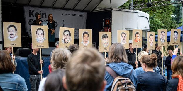 Auf einer Kundgebung vor dem NSU-Prozess werden Bilder der NSU-Opfer hochgehalten