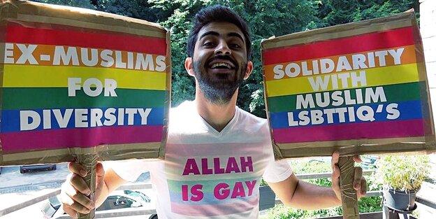 Ein Mann lacht und hält zwei Schilder in je einer Hand