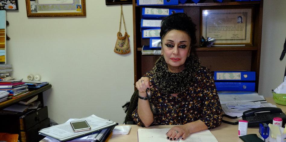 eine Frau sitzt hinter einem Schreibtisch