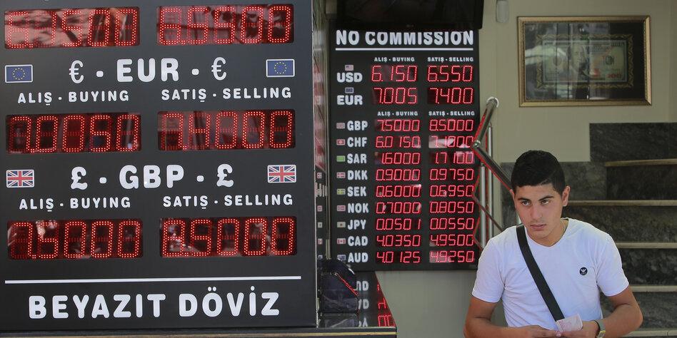 Mann vor Anzeigetafel mit den Wechselkursen in Türkei