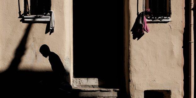 der Schatten eines gebückt gehenden Mannes auf einer Hauswand