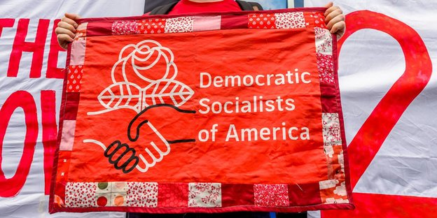 Mann hält Banner mit Democratic Socialists of America