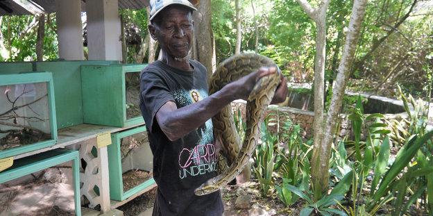 Ein Mann hält eine Giftschlange in seinen Händen