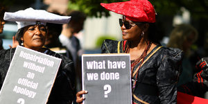 "Bei Herero-Nama-Protest, zwei Frauen mit Schildern ""What have we done?"" und ""Repatriation without an official apology?"""