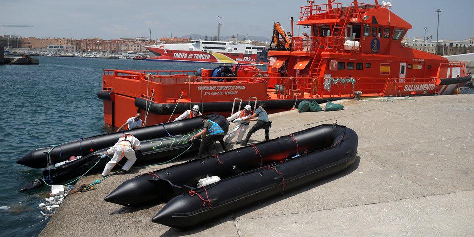 Zwei schwarze Schlauchboote vor einem orange farbenen Grenzschutzschiff