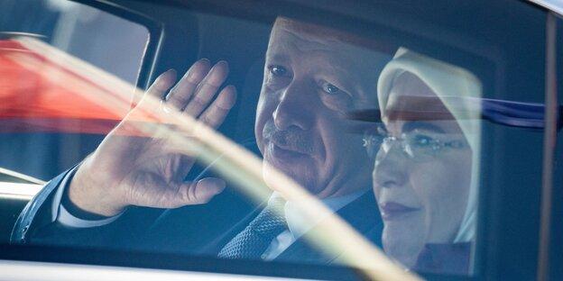 Erdoğan und seine Frau Emine Erdoğan sitzen in einem Auto, er winkt