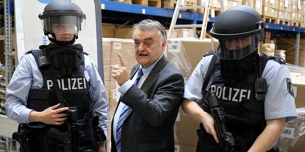 Herbert Reul (CDU, M), Nordrhein-Westfalens Innenminister, steht zwischen zwei Polizisten, die ballistische Schutzhelme tragen.