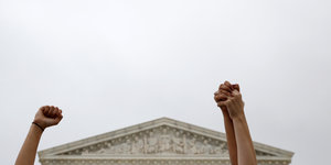 Demonstrantinnen vor dem Supreme Court in Washington haben ihre Arme in die Luft gehoben