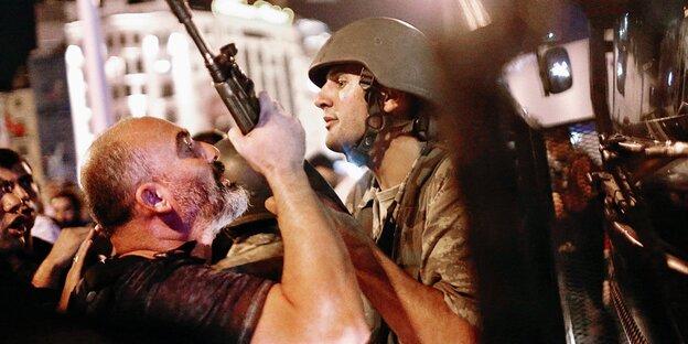 Ein Bürger greift nach dem Maschinengewehr eines jungen Soldaten