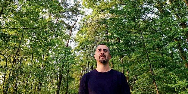 Yavuz Ulaş steht in einem Wald