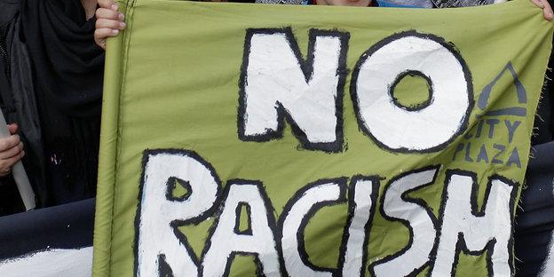 """Ein Junge hält ein Transparent mit der Aufschrift """"No Racism"""" hoch"""