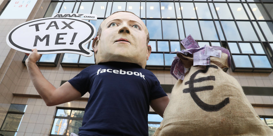 Ein Mann mit Mark-Zuckerberg-Maske hält ein Schild auf dem