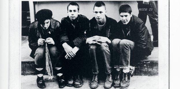 """Ein schwarz-weiß Foto, auf dem vier junge Männer, die Band """"Beastie Boys"""" nebeneinander sitzen"""