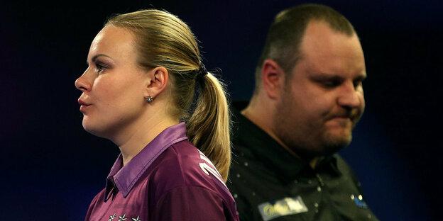 Anastassija Dobromyslowa hat Dartspfeile in der Hand, hinter ihr steht Ryan Joyce
