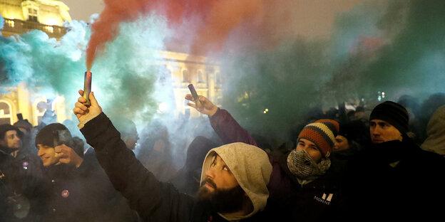 Menschen auf einer Demo mit Rauchsignalgebern