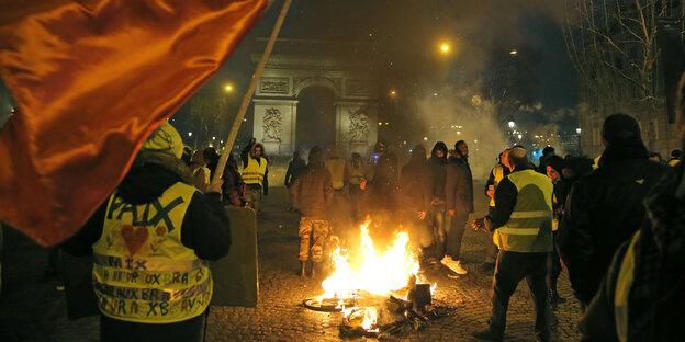 DemonstrantInnen mit gelben Westen stehen neben einem brennenden Fahrrad auf der Avenue des Champs-Elysée