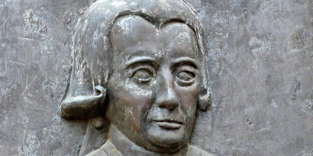 Bronzetafel eines streng blickenden Mannes mit Perücke.