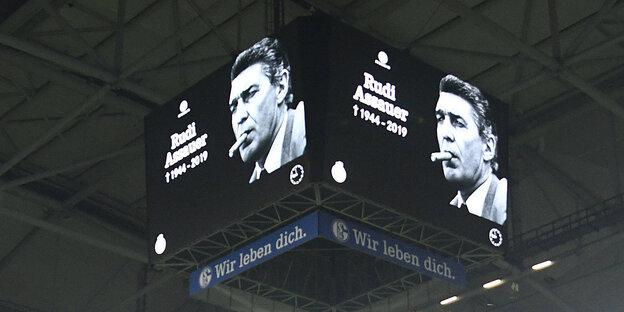 Auf dem Videowürfel eines Stadions ist ein Bild von Rudi Assauer zu sehen