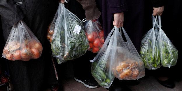 Menschen stehen in einer Schlange und halten Plastiktüten voll mit Gemüse
