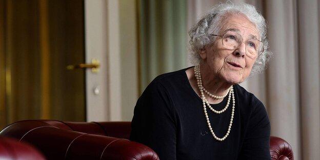 Die Kunderbuchautorin Judith Kerr sitzt auf einem roten Ledersofa