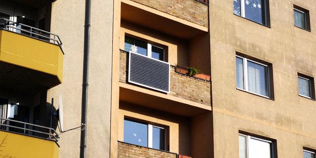 Blick auf ein Wohnhaus. An einem Balkon ist ein Solarmodul erkennbar