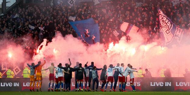Die Spiler des HSV lassen sich von Fans mit bengalischen Feuern feiern.