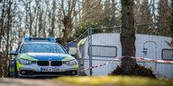 Ein Polizeiwagen parkt neben einem Campingtrailer, der als mutmaßlicher Tatort abgesperrt ist