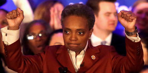 Lori Lightfoot hebt die Fäuste in die Luft