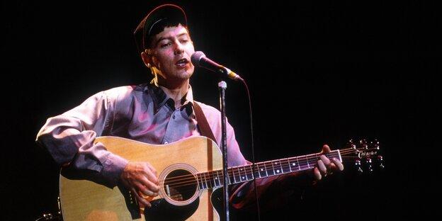 Ein Sänger steht mit Gitarre auf einer Bühne