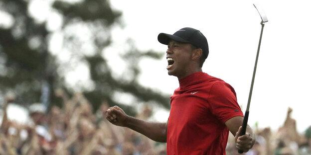 Tiger Woods freut sich, er hält einen Golfschläger in die Höhe